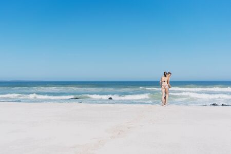 Young couple in swimsuits entering the ocean on a wide open deserted sandy beach in Cape Town South Africa with a calm sea and gentle breaking waves