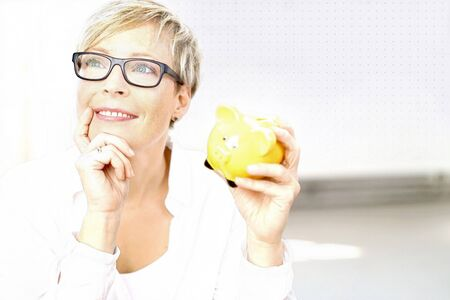 Thoughtful smiling short-haired woman holding yellow piggy bank Stock Photo
