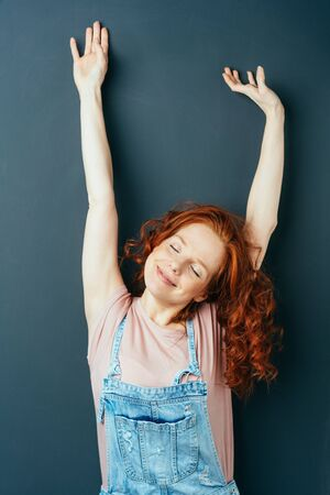 Happy relaxed young woman stretching her arms above her head with closed eyes and a contented smile over a dark studio background with copy space Stock Photo