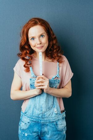 Pretty pert young redhead woman in dungarees looking at the camera with a playful grin as she holds a builders ruler over a dark studio background