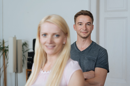 Portrait of young man and blonde cheerful woman standing in domestic room Stock Photo