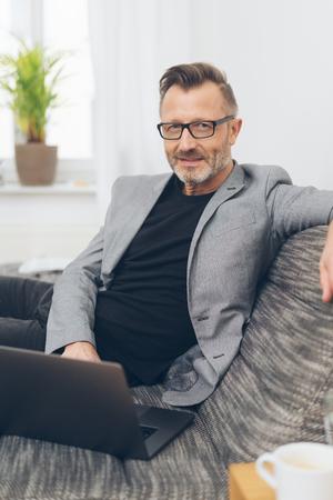 Portrait of mature man wearing grey jacket using laptop while sitting on sofa