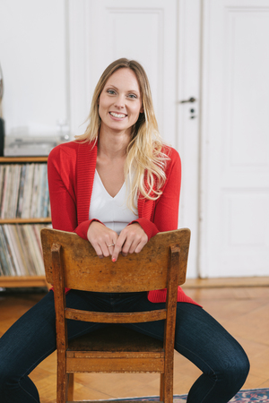 Portrait of blonde smiling woman wearing red cardigan sitting on chair Stok Fotoğraf