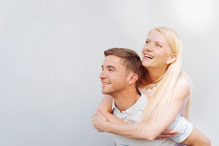Happy joyful affectionate young couple piggy backing in a profile view in front of a white wall and copy space