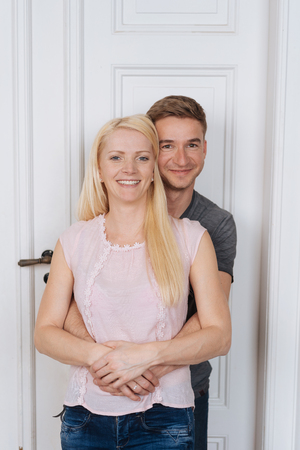 Portrait of young smiling couple standing against white door at home Foto de archivo