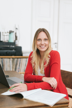 Portrait of cheerful blonde woman wearing red cardigan sitting in front ot laptop Stok Fotoğraf
