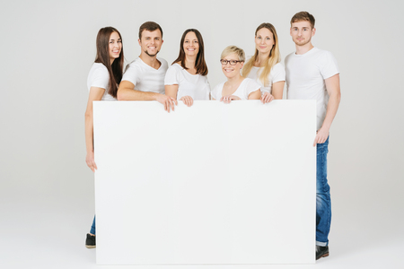 Group of casual friends in jeans holding a large blank white sign in front of them with copy space as they smile happily at the camera