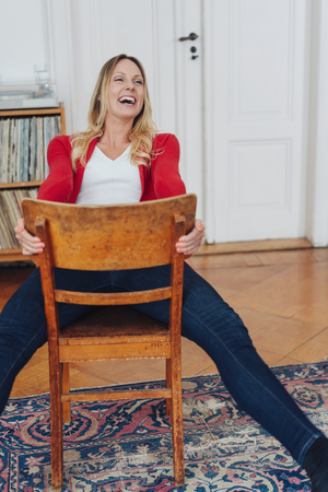 Young woman enjoying a hearty laugh at a joke as she relaxes sitting on a reversed wooden chair at home in the living room Stok Fotoğraf