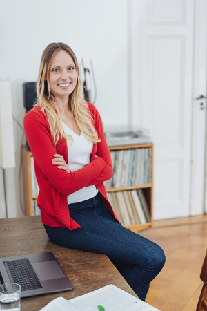 Smiling friendly young woman with long blond hair sitting with folded arms perched on a wooden table with laptop smiling at the camera