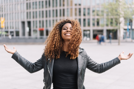 Happy young African woman celebrating with outstretched arms, eyes closed and a beaming smile in a high key urban street Stock Photo