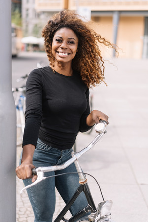 Cute young African woman with a beaming smile holding a bicycle in a high key urban street