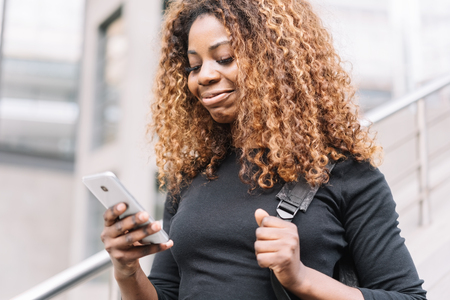 Young African woman using an escalator in town as she checks a text message on her mobile phone with a happy smile Stock Photo