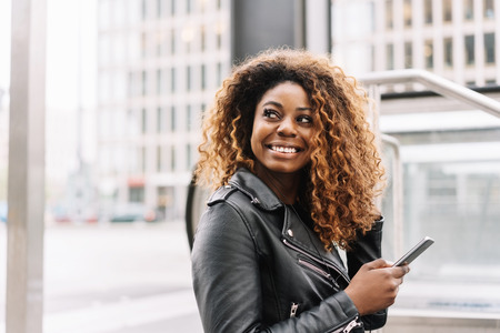 Portrait of young cheerful African American woman wearing leather jacket holding mobile phone
