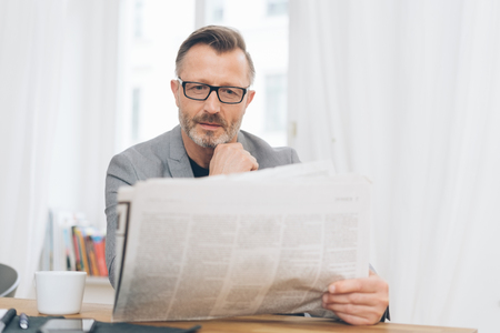 Middle-aged man immersed in reading the newspaper as he sits at a table at home with a cup of coffee