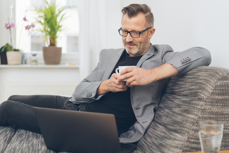 Portrait of mature man having coffee while sitting on sofa with laptop 写真素材