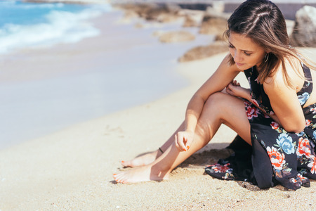 Young woman daydreaming and playing with sea sand as she sits on a tropical beach in the warm sunshine