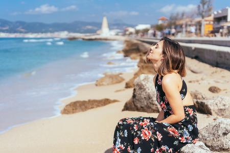 Pretty young woman soaking up the summer sun as she sits relaxing on rocks on a sandy beach in a seaside resort