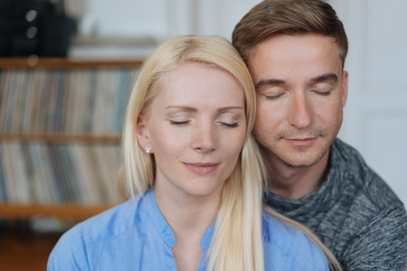 Peaceful contented loving couple enjoying a quiet moment together standing with their heads touching, closed eyes and serene expressions Stock Photo