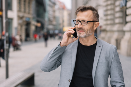 A mature professional man with glasses talking on a smart phone in an urban street scene.