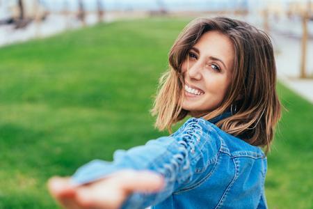 Heureuse jeune femme tenant sa main avec un sourire invitant alors qu'elle regarde par-dessus son épaule en mettant l'accent sur son visage Banque d'images