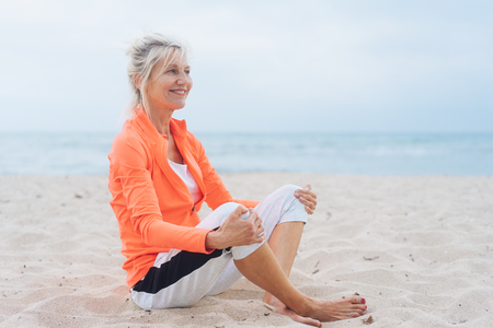 Happy supple mature blond woman seated in the golden sand on a beach looking to the side of the frame with a beaming smile against an ocean backdrop