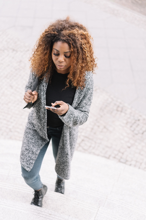 Young African woman walking up a flight of external steps reading a message on her mobile phone viewed from above looking down