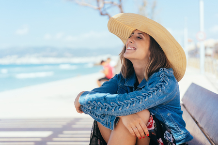 Happy vivacious young woman in a straw sunhat sitting on a seafront promenade overlooking the ocean
