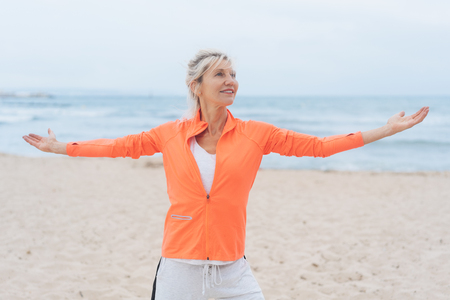 Fit slender blond woman working out on a beach standing with outstretched arms and ocean backdrop
