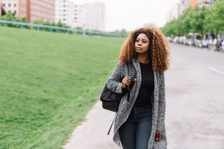 Portrait of young black woman with curly hair walking along street