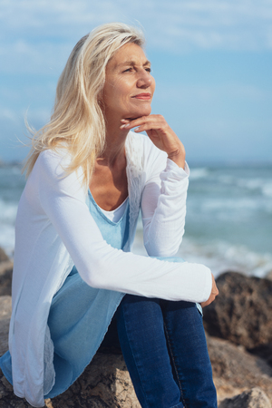 Attractive mature woman relaxing at the seaside sitting on a rocky shoreline with her chin on her hand looking into the distance with a smile