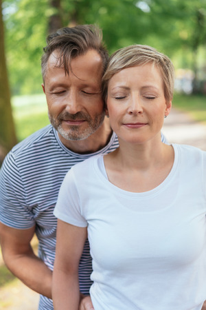 Portrait of a happy middle-aged couple in love daydreaming together with eyes closed outdoors in a summer day Stock Photo