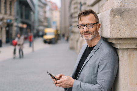 A mature professional, metro man with glasses texting on a smart phone in an urban street scene while looking at the camera.