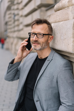 A mature professional, metro man with glasses talking on a smart phone in an urban street scene.