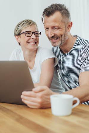 Happy middle-aged couple in love smiling while watching together a funny video on the laptop at home
