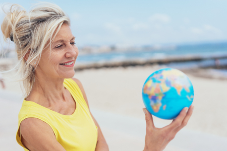 Smiling attractive blond woman standing on a sandy tropical beach with a world globe raised in her hand in a conceptual image