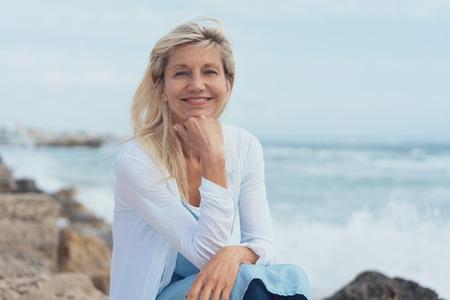 Lächelnde freundliche Frau, die sich auf Felsen am Strand an einem nebligen Tag entspannt, der mit ihrem Kinn sitzt, das auf ihrer Hand ruht, die Kamera betrachtet