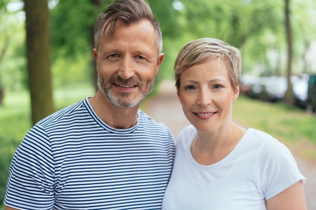 Portrait of a happy and handsome handsome middle-aged man wearing striped summer T-shirt while looking at camera next to his beautiful wife