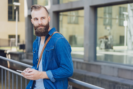 Casual young bearded man standing leaning against a railing in town watching to the side with a thoughtful expression Stock Photo