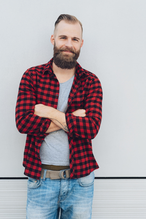 Smiling confident bearded man in red plaid shirt standing with folded arms in front of a white wall