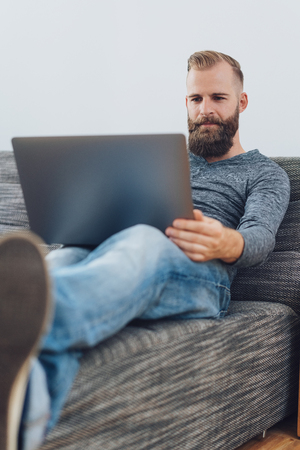 Young bearded man relaxing with his feet up on a comfortable couch at home as he works on his laptop computer