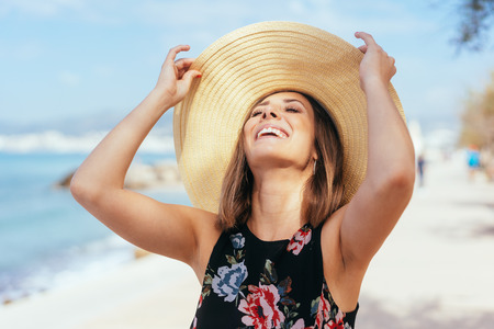 Laughing carefree young woman in a wide brimmed straw hat standing on the sand at the beach with her head thrown back