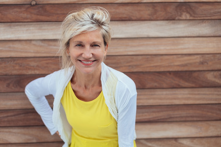 Attractive older blond woman with a vivacious smile standing in front of a wooden wall leaning forwards staring into the camera Stock Photo