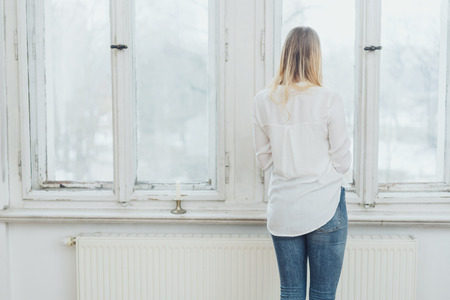 Rear view of blonde woman standing by window at home in bright room Stock Photo