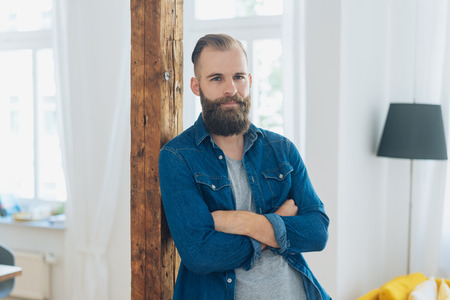 Relaxed confident young bearded man leaning against a wooden interior beam with folded arms looking thoughtfully at the camera Stock Photo
