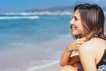 Happy young woman relaxing a the beach sitting on the sand looking out over the ocean with a beaming smile with copy space