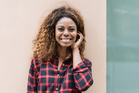 Portrait of young cheerful black woman wearing checked shirt