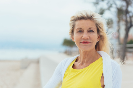 Attractive blond woman on a breezy beach seated on the steps of the promenade overlooking the ocean turning to smile at the camera
