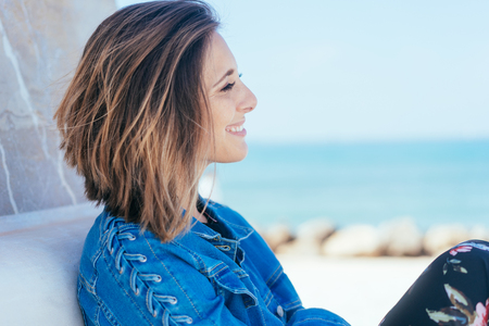 Smiling young woman relaxing on a bench overlooking a beach in a close up profile view