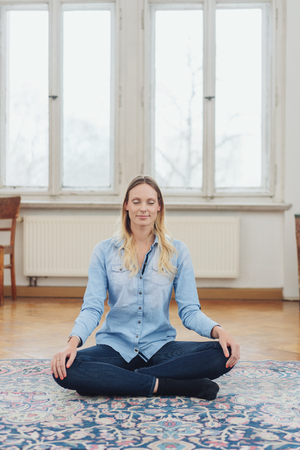 Blonde relaxed woman sitting cross-legged on floor at home