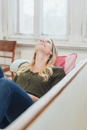 Relaxed young woman enjoying some quality time lying on a comfortable sofa at home looking up thinking